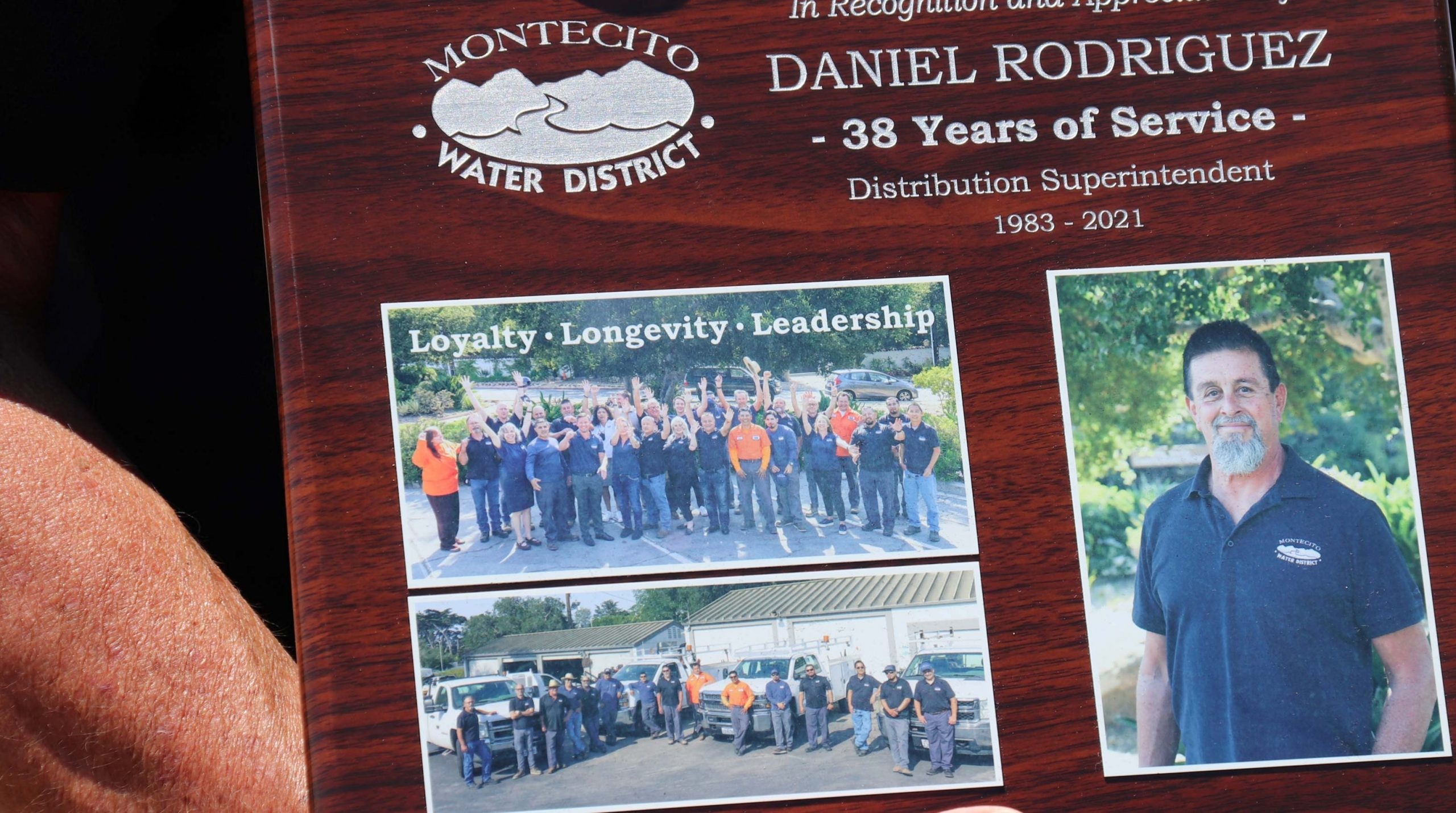 Distribution Superintendent Daniel Rodriguez holding plaque commemorating his retirement and 38 years of service.