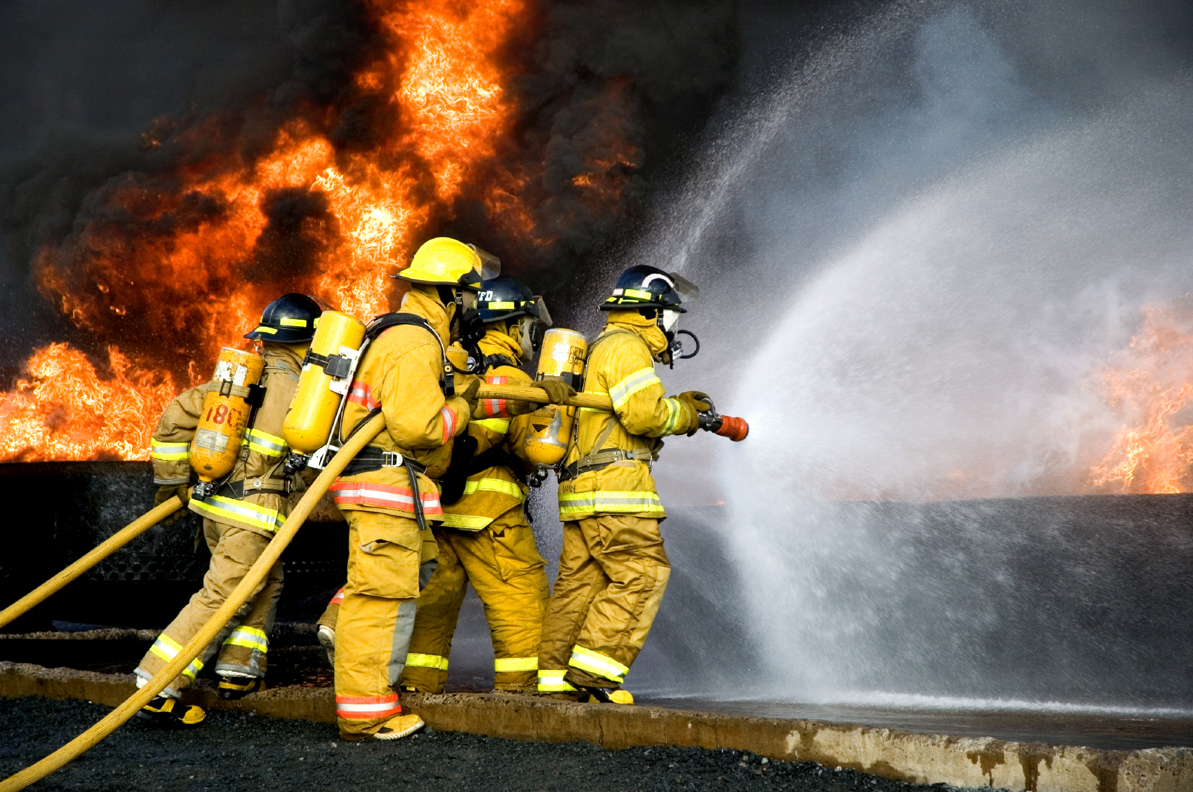 Firefighters spraying water into a fire