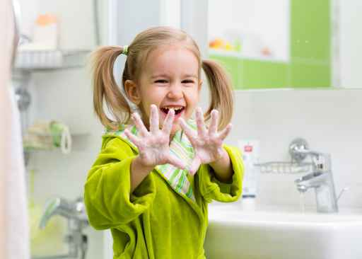 Young girl showing hands after washing at a sink