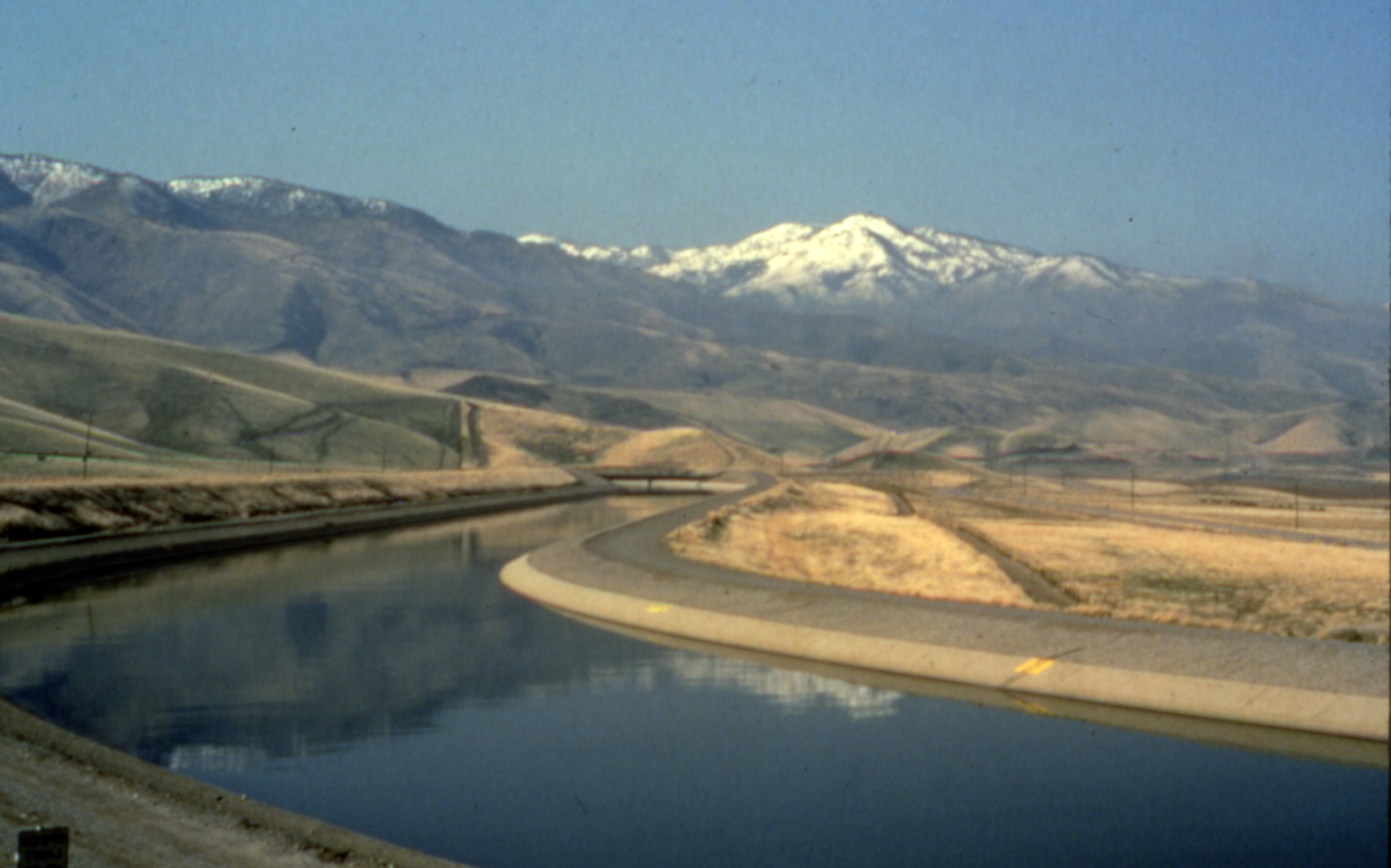 State Water Project canal with snow topped mountains in background