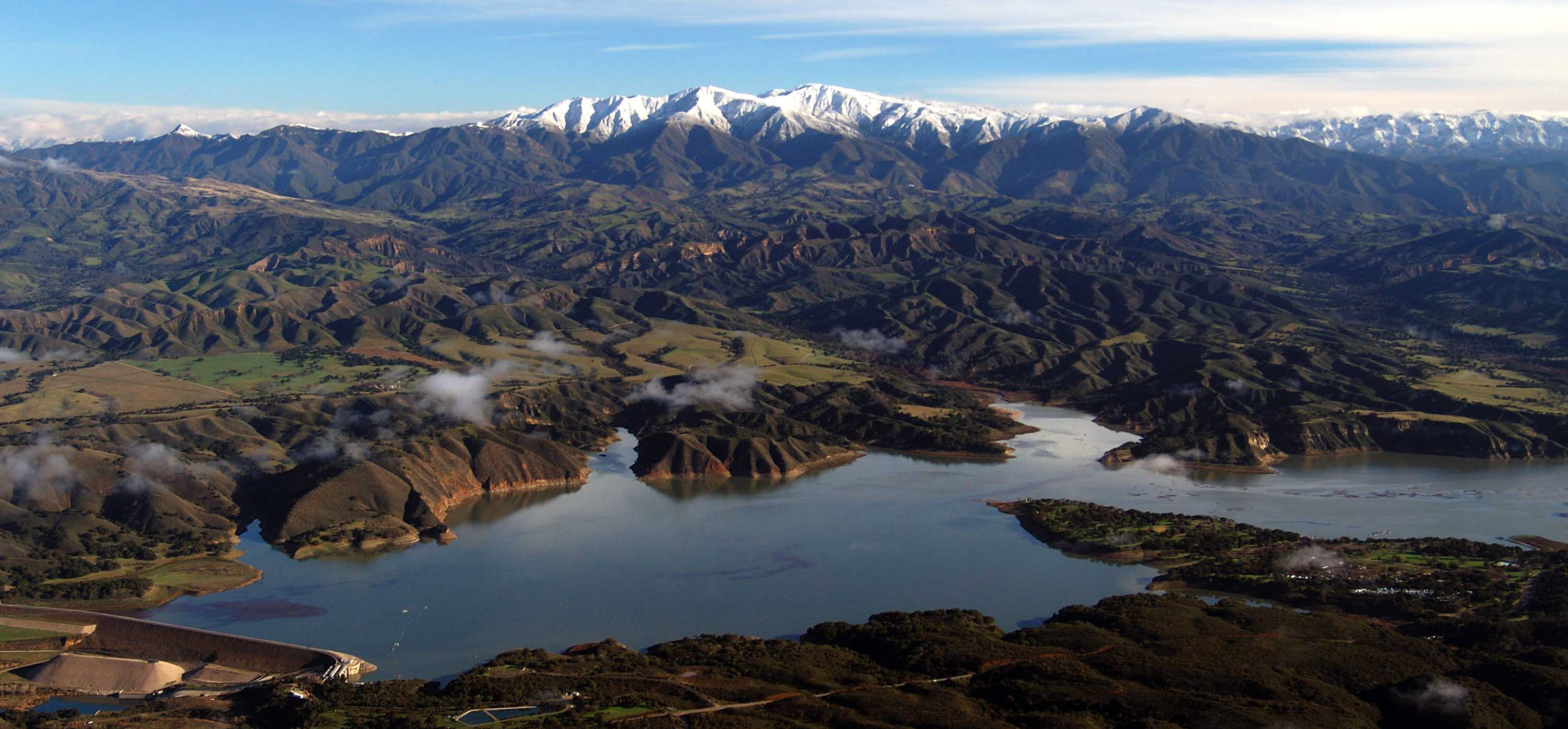 Aerial photo of Lake Cachuma in winter with snow capped mountains in background